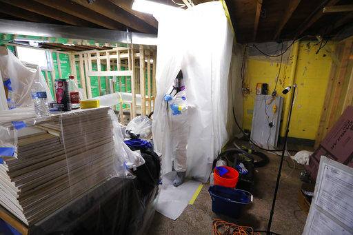 Workers prepare for an asbestos abatement in Howell, Mich.
