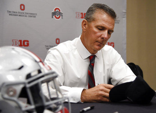 Ohio State University head coach Urban Meyer autographs a hat at the Big Ten Conference NCAA college football media days in Chicago, Tuesday, July 24, 2018.