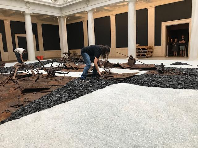 "Cristobal Martinez arranges coal in July at the Carnegie Museum of Art for ""Through Smoke and Tangled Waters, We Carried Fire Home."""