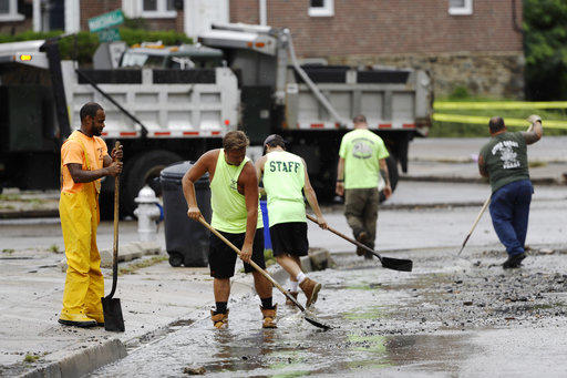 Workers clean up debris swept into the street during flooding in Upper Darby, Pa., Monday, Aug. 13, 2018.