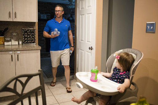 In this Aug. 1, 2018 photo, Dan McDowell carries water to his refigerator as his 16-month-old daughter Caroline looks on at their home in Horsham, Pa.