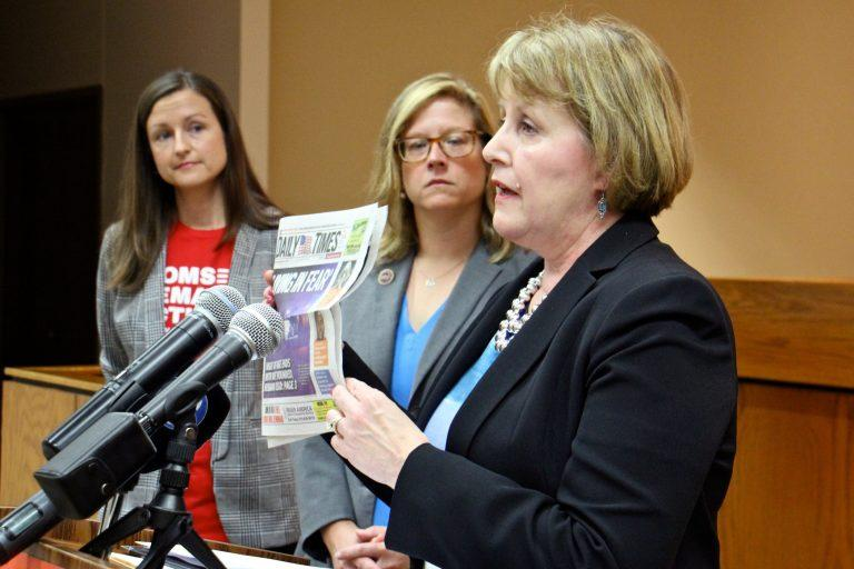 Cathy Stone, right, Executive Director of the Domestic Abuse Project of Delaware County holds up a headline-grabbing example of domestic abuse during a press conference to promote House Bill 2060.