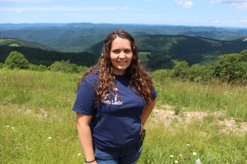 Lindsay Knotts standing on a hilltop above her family farm in Tucker County. The Knotts have been farming in Tucker County for several generations.