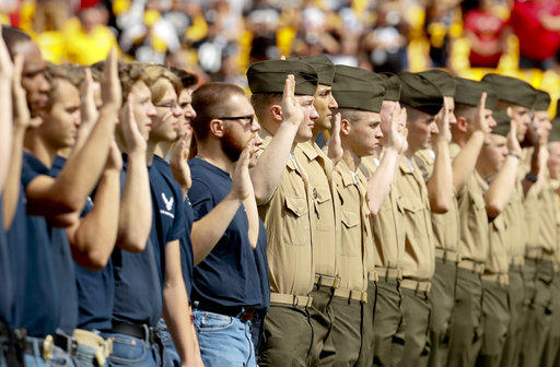 Military recruits take their oath as they are sworn in at an NFL Football game between the Pittsburgh Steelers and the Kansas City Chiefs, Sunday Sept. 16, 2018, in Pittsburgh.