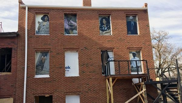 This Feb. 17, 2017 photo shows images in the windows of the August Wilson House in Pittsburgh. Wilson lived in the upstairs apartment at the house from his birth in 1945 until 1958 with his mother and siblings.