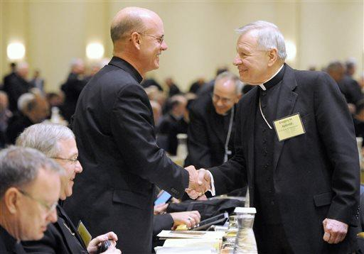 Bishop Kevin C. Rhoades, left, of Fort Wayne-South Bend, Ind. and Archbishop Gregory M. Aymond of New Orleans shake hands at the start of a U.S.  Conference of Catholic Bishops general meeting on Monday, Nov. 10, 2014.