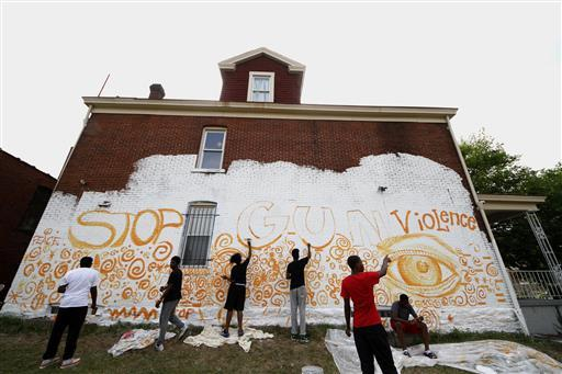 Young adult artists in Homewood paint a mural on the side of a building as part of a community wide 10 mural project in 2016. Gun violence prevention is among the many issues central to the Women's Center and Shelter's mission.