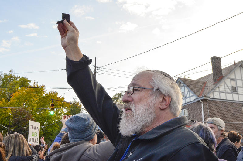 Rabbi Yitzhak Husbands-Hankin of Eugene, Oregon, holds a torn piece of black paper in the air during Tuesday's march. People in the crowd participated in Kriah, a Jewish tradition to express grief and anger at the loss of a loved one.