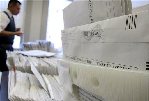 Absentee ballots are sorted in Milwaukee. In Pennsylvania, officials are promoting ways for state residents living overseas to obtain absentee ballots.