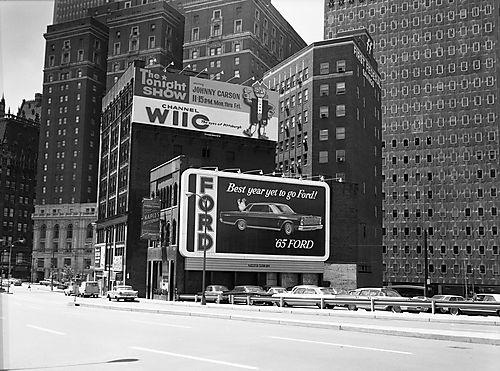 Billboards advertising Ford automobiles and the Tonight Show with Johnny Carson line the sides of two downtown Pittsburgh buildings.