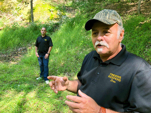 In this Sept. 20, 2018 photo, Dennis Parada, right, and his son Kem Parada, stand at the site of the FBI's dig for Civil War-era gold in Dents Run, Pa.