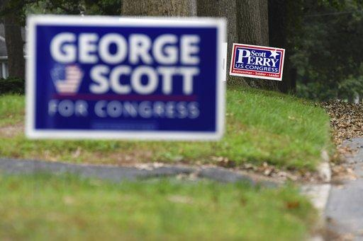 Campaign signs for Republican U.S. Rep. Scott Perry, of Pa., and Democratic challenger George Scott sit on lawns in Camp Hill, Pa.