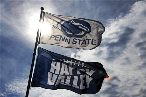 Penn State banners hang over a tailgate in the parking lot surrounding Beaver Stadium before an NCAA college football game in 2015.