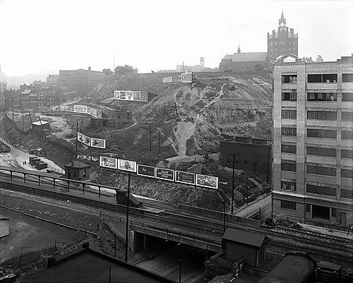 A view looking east from Second Avenue at the Bluff. The image also shows billboards on the Bluff and Old Main of Duquesne University. When the steel industry dominated the region's economy, people gave little thought to the impact of billboards.