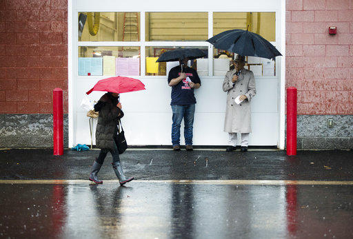 A voter walks in the rain from her polling place in Langhorne, Pa. on Tuesday, Nov. 6, 2018.