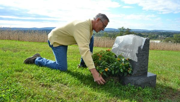 Jeff Sterner adjusts a flower displays on his son Joshua's grave. Josh was 19 in 2012 when he died by suicide.
