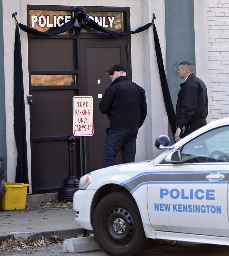 Police officers arrive at the door of the New Kensington Police station, which was draped in black Monday, Nov. 20, 2017, honoring 25-year-old Officer Brian Shaw. Shaw, who was hired full-time in June, was shot and killed Friday during a traffic stop.