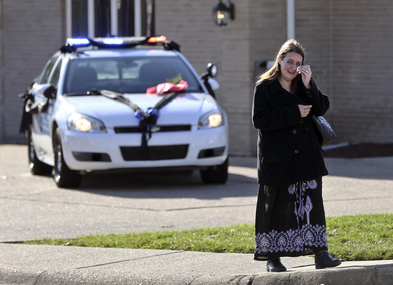A woman wipes her eye as she walks past a police car draped in black after leaving a visitation for New Kensington Police Officer Brian Shaw at a funeral home Monday, Nov. 20, 2017 in Lower Burrell. Shaw was shot and killed during a traffic stop Friday.