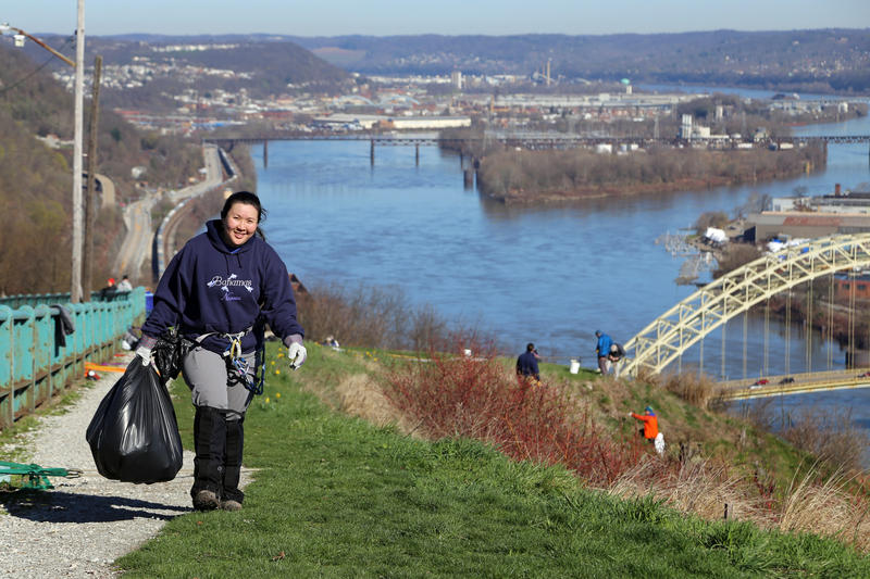 Nancy Tran, 36, of Dormont carries a full trash back to fellow volunteers with the Explorers Club of Pittsburgh on April 8. The group takes on a small swath of Mt. Washington hillside every year through a partnership with the Pittsburgh Parks Conservancy.