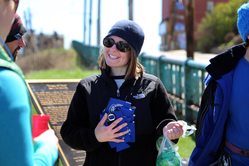 Environmental chair Ginette Walker Vinski of the Explorers Club of Pittsburgh hands out koozies after the group's 25th annual trash pick-up and rappel off Grandview Avenue on Saturday, April 8, 2017.