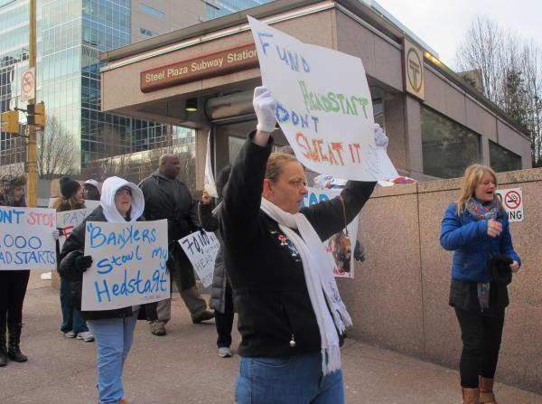Protesters with One Pittsburgh rally outside the BNY Mellon building in downtown Pittsburgh Friday.