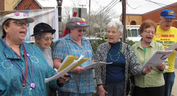 """The """"Raging Grannies,"""" including members Edith Beill (second from left) and Eva Havlicsek (third from left) sing a song in protest of military spending at their Tax Day protest outside of the Squirrel Hill Post Office."""