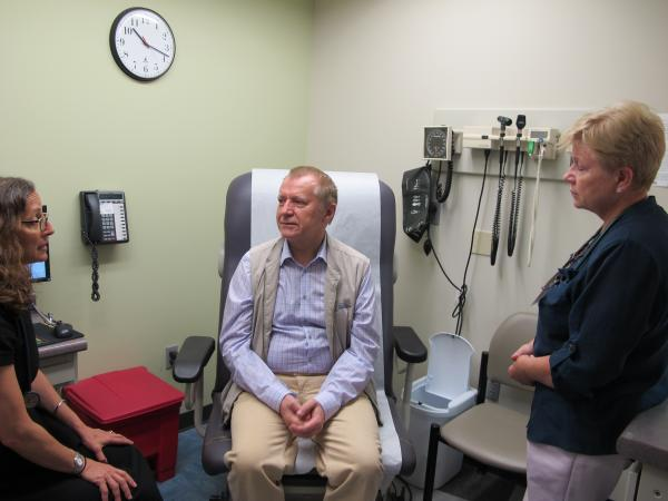 At the Squirrel Hill Health Center, Medical Director Andrea Fox treats patient Vladzimir Shein while Medical Office Assistant Rita Bidrat translates from Russian to English.