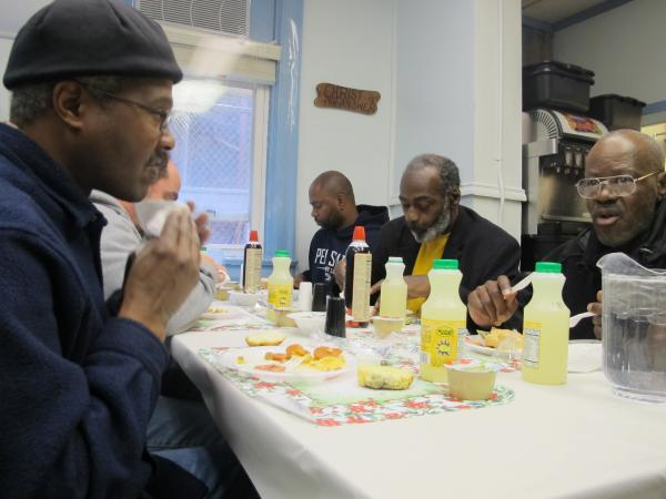 Troy Millbourne (left) enjoys a meal with (left to right) Michael Tiller, David Kelley, and Frankie Harris at Light of Life Rescue Mission on the North Side.
