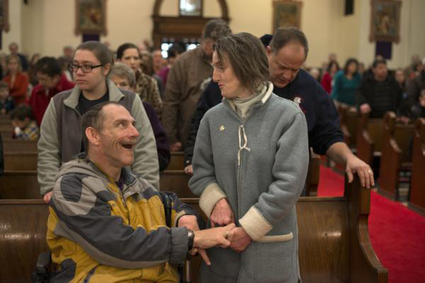 Bob and Tina Norris exchange the sign of peace during Mass at Holy Spirit Church in Millvale.