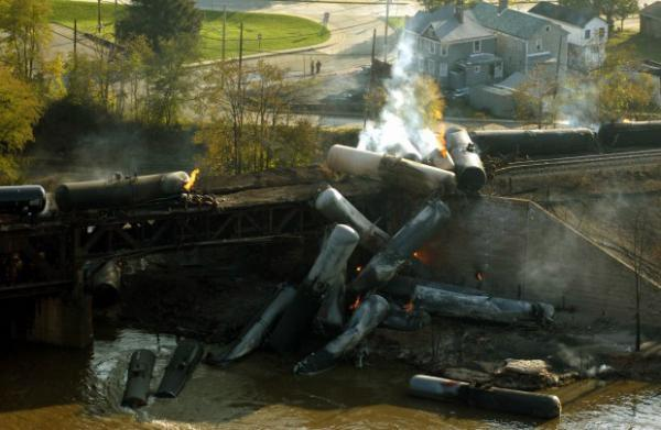Flames continue to burn a day after a Norfolk Southern train derailed on Oct. 21, 2006, in New Brighton, Pa.