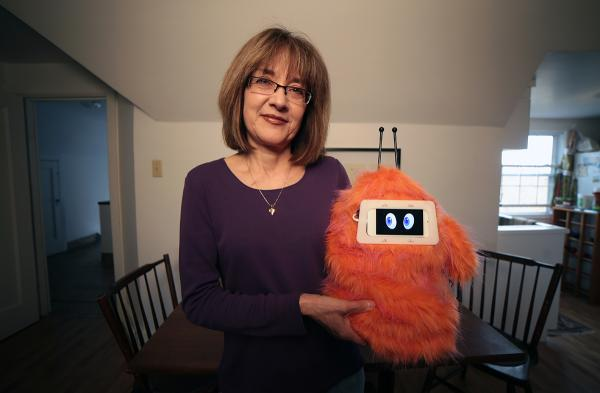 Tess Lojacono holds Romibo, a social therapy robot designed to aid therapists and teachers working with children with special needs.