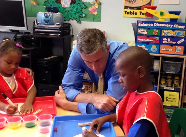 U.S. Secretary of Education Arne Duncan talks with children from the Hug Me Tight Childlife Center in the Hill District.