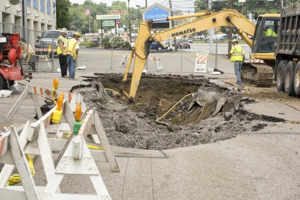 Crews work Wednesday on large sinkhole that opened up in the parking lot of a McKnight Road business.