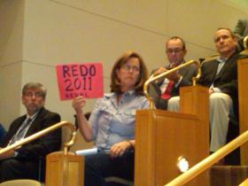 A woman holds up a sign Tuesday night that urges Mecklenburg County commissioners to redo the 2011 property revaluation.