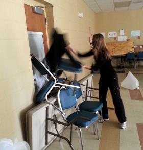 A teacher stacks barricades a classroom door with tables and chairs, in a training simulation.