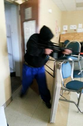 An instructor in a paintball mask barges through the barricaded door and fires a pellet gun to simulate a shooting.