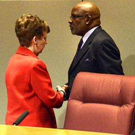 Harry Jones shakes hands with Commission Chairwoman Pat Cotham after his firing.