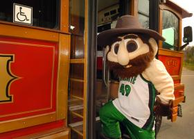 Norm the Niner, the 49ers mascot, catches the University shuttle. Before Norm, the University's mascot was an owl because college  students attended classes in the evening in places like Charlotte's Central High School (after the high school students left for the day) for the first few years of its existence.
