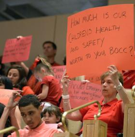 Advocates for school nurse funding held up signs at a meeting of the Mecklenburg County Board of Commissioners.