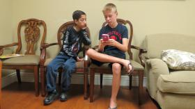 Menhaj watches his host brother, Gavin Gunter, also 12, play a game on his mom's phone.