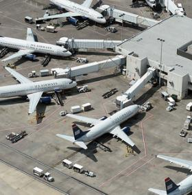 US Airways jets are parked at the terminal at Charlotte Douglas International Airport Tuesday, May 7, 2013.