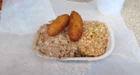 "A tray of Lexington-style chopped pork barbecue, served with ""red"" slaw and hush puppies."