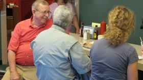 Lexington Barbecue founder Wayne Monk visits with customers at the counter at his restaurant.