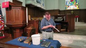 Organ builder Phil Parkey makes minute adjustments to pipes as small as a pencil and as large at 16 feet.