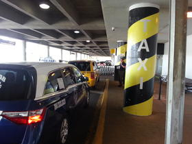 Taxis line up at the airport curb