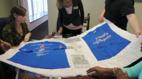 Librarians and students look at a piece of an AIDS memorial quilt donated to the special collections at the UNC Charlotte's library. The quilt is from a local family in memory of Paul Sumrell, who was battling AIDS and died on December 3, 2004.