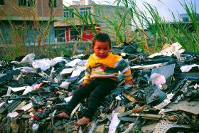 In this photo from 2001, a migrant child sits atop a pile of unrecyclable computer waste imported to Guiya, China, from other countries.