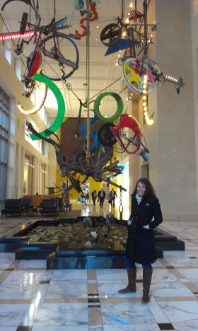 Nicole Bartlett of the Arts and Science Council in front of Jean Tinguely's Cascade sculpture in the lobby of the Carillon building.
