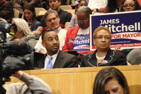 Candidate James Mitchell and some of his supporters holding yard signs were in attendance at a special city council meeting on April 7 announcing the selection of the new mayor.