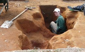 An archaeologist in one of the holes recovered at Camp Asylum.